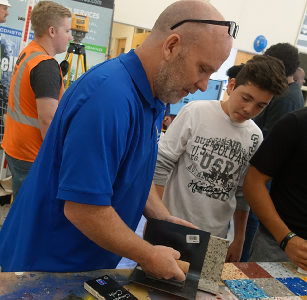Company News: Superintendent demonstrating terrazzo to high school students